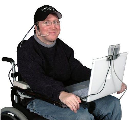 A man using puff n' sip adaptive technology to control a keyboard