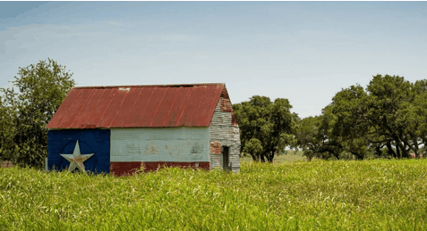 A farmhouse with a texas flag painted on it